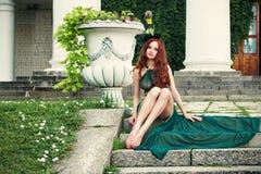 Frau mit den langen Beinen, die in einem grünen Kleid sitzen Stockfoto
