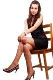 Frau mit den netten reizvollen Fahrwerkbeinen, die auf Stuhl sitzen Lizenzfreie Stockfotografie
