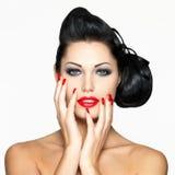 Frau mit den roten Lippen, den Nägeln und Frisur Stockfotografie