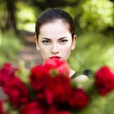 Frau mit den roten Lippen, die Blumen geben Stockfotos