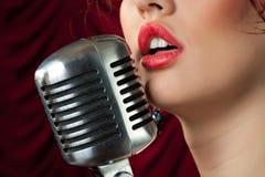 Frau mit den roten Lippen singend im Mikrofon Stockbild