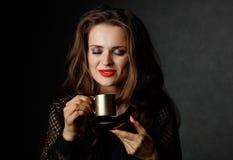 Frau mit den roten Lippen Tasse Kaffee auf dunklem Hintergrund genießend Stockfotografie