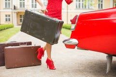 Frau mit den sexy Beinen, die einen Weinlesekoffer halten Lizenzfreie Stockfotos