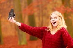 Frau mit der alten Weinlesekamera, die selfie Foto macht Stockfotografie