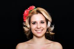 Frau mit der Blondine legend und mit roten Blumen auf einem dunklen Hintergrund eingefaßt Stockbilder