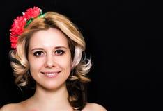 Frau mit der Blondine legend und mit roten Blumen auf einem dunklen Hintergrund eingefaßt Lizenzfreies Stockfoto