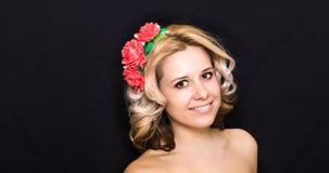 Frau mit der Blondine legend und mit roten Blumen auf einem dunklen Hintergrund eingefaßt Stockfotos