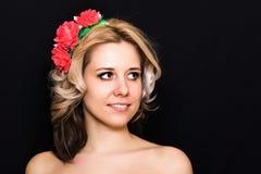 Frau mit der Blondine legend und mit roten Blumen auf einem dunklen Hintergrund eingefaßt Stockfoto