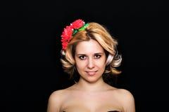 Frau mit der Blondine legend und mit roten Blumen auf einem dunklen Hintergrund eingefaßt Lizenzfreie Stockfotos