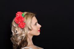 Frau mit der Blondine legend und mit roten Blumen auf einem dunklen Hintergrund eingefaßt Stockfotografie