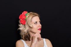 Frau mit der Blondine legend und mit roten Blumen auf einem dunklen Hintergrund eingefaßt Lizenzfreie Stockbilder