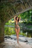 Frau mit der dünnen perfekten Zahl, die im Designbadeanzug am exotischen Standort von Gebirgsfluss aufwirft Stockbilder