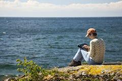Frau mit der digitalen Tablette, die durch den See sitzt Lizenzfreie Stockfotografie