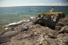 Frau mit der digitalen Tablette, die durch den See sitzt Lizenzfreie Stockfotos