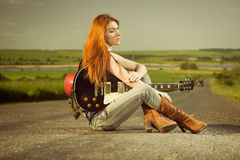 Frau mit der Gitarre, die am Asphalt sitzt stockfotografie