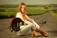 Frau mit der Gitarre, die am Asphalt sitzt lizenzfreie stockfotos