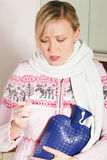 Frau mit der Grippe, die ihre Temperatur nimmt Stockfotos