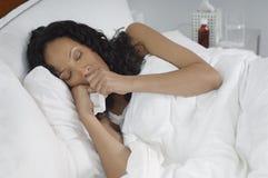 Frau mit der Grippe, die im Bett liegt stockbilder