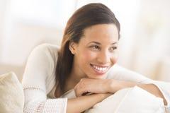 Frau mit der Hand auf Chin Looking Away At Home Stockfoto