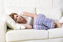 Frau mit der Hand auf ihrer leidender Magenklammer und -zeitraum des Bauches oder des Bauches schmerzen Lizenzfreies Stockfoto