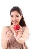 Frau mit der Hand, die den roten Apfel, Daumen aufgebend hält Stockfoto