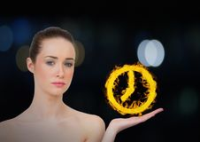 Frau mit der Hand oben mit Uhrfeuerikone vorbei Dunkler bokeh Hintergrund Stockbilder