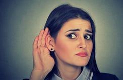 Frau mit der Hand zur Ohrgeste sorgfältig hörend lizenzfreie stockfotos