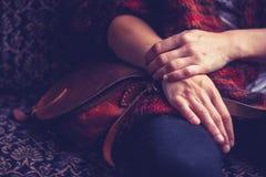 Frau mit der Handtasche, die auf altem Weinlesesofa sitzt stockfotografie