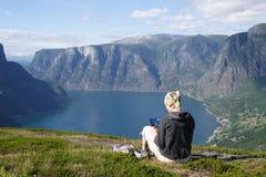 Frau mit der Karte, die auf die Oberseite des Berges sitzt Stockfotografie