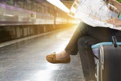 Frau mit der Karte, die neben Eisenbahn in der Bahnstation sitzt Stockfotografie