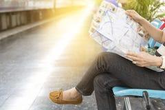 Frau mit der Karte, die neben Eisenbahn in der Bahnstation sitzt Lizenzfreie Stockfotos