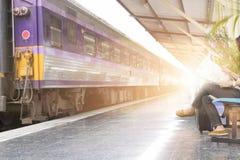 Frau mit der Karte, die neben Eisenbahn in der Bahnstation sitzt Stockbilder