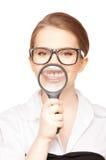 Frau mit der Lupe, die Zähne zeigt Stockbild