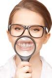 Frau mit der Lupe, die Zähne zeigt Stockfotografie