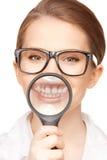 Frau mit der Lupe, die Zähne zeigt Lizenzfreie Stockfotografie