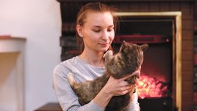 Frau mit der netten Katze, die nahe Kamin stillsteht stock video footage