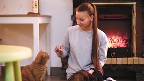 Frau mit der netten Katze, die nahe Kamin stillsteht Viele Katzen Katzendame des jungen Mädchens der alleinstehenden Frau stock footage