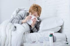 Frau mit der niesenden Nase, die im Gewebe auf dem Bett erleidet die kalten Grippevirussymptome haben Medizin durchbrennt, tablet Stockfotografie
