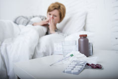 Frau mit der niesenden Nase, die im Gewebe auf dem Bett erleidet die kalten Grippevirussymptome haben Medizin durchbrennt, tablet Lizenzfreie Stockbilder