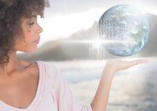 Frau mit der offenen Palmenhand, die Welterdkugelschnittstelle hält stockfotografie