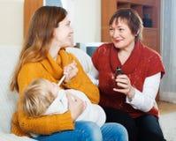 Frau mit der reifen Mutter, die dem unwohlen Baby Sirup gibt Stockfotos