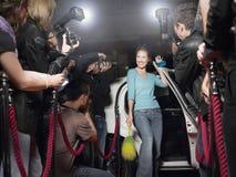 Frau mit der Reinigungsanlage, die in Front Of Paparazzi aufwirft Stockfoto