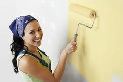 Frau mit der Rolle, die gelbe Farbe auf einer Wand anwendet Stockbild