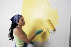 Frau mit der Rolle, die gelbe Farbe auf einer Wand anwendet Stockfotografie