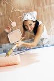 Frau mit der Rolle, die rosa Farbe auf einer Wand anwendet Lizenzfreie Stockfotos