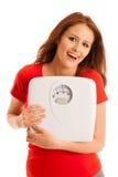Frau mit der Skala glücklich mit ihrem Gewicht lokalisiert über weißem backg Stockfoto