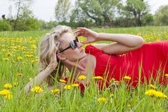 Frau mit der Sonnenbrille, die in einer Wiese liegt Stockfoto