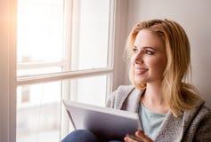 Frau mit der Tablette, die auf Fensterbrett, sonniger Tag sitzt Stockbild