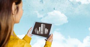 Frau mit der Tablette, die weiße Gebäude gegen Himmel mit Wolken zeigt Stockfoto
