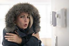 Frau mit der warmen Kleidung, die der Kälte innerhalb des Hauses glaubt lizenzfreie stockfotos